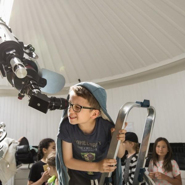 Kinderen kijken door de grote telescoop van Sonnenborgh
