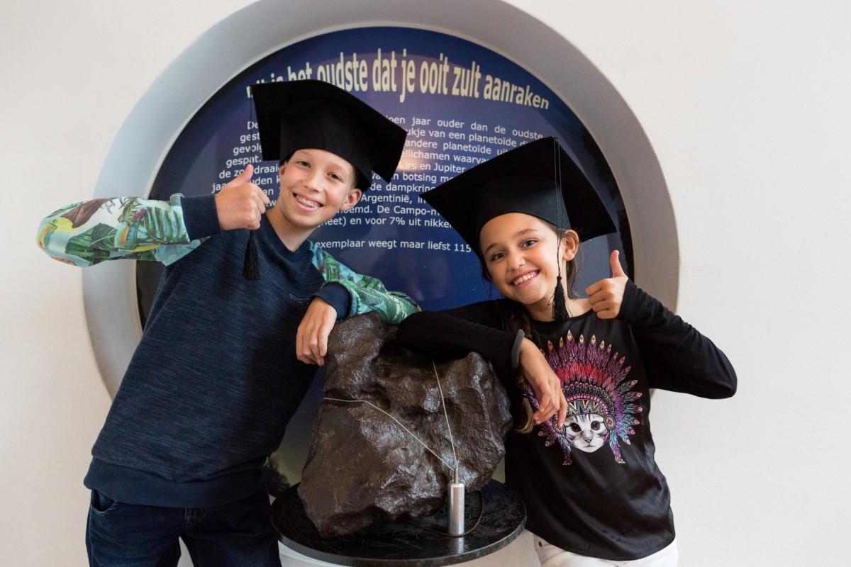 Vloggers van de MuseumJeugdUniversiteit bij de grote meteoriet