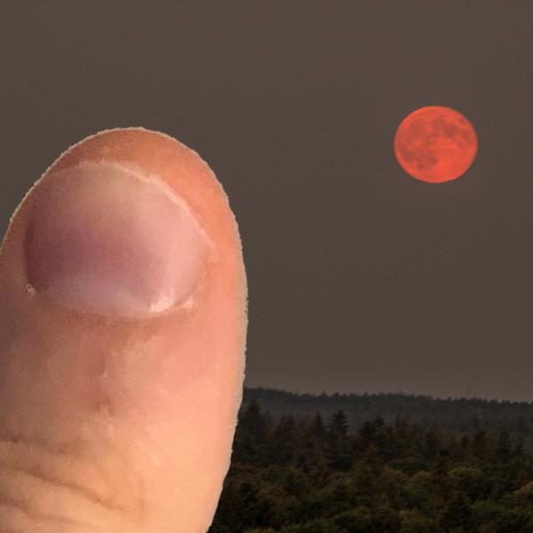 De volle maan naast een duim