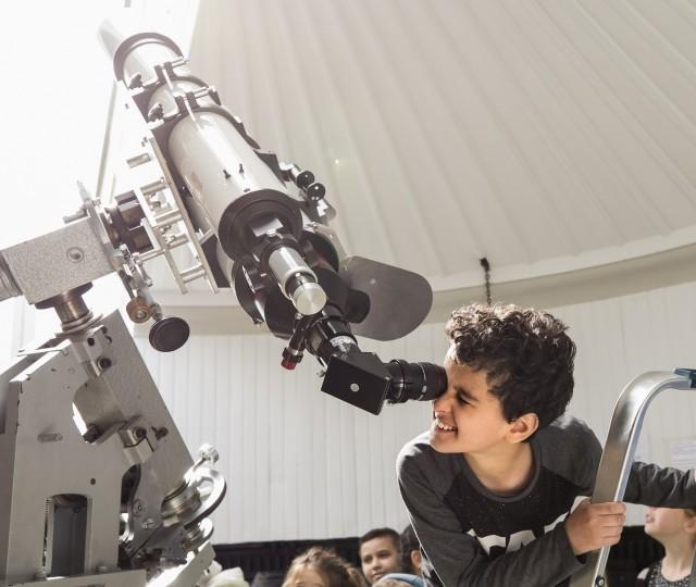 Jongetje kijkt door een telescoop